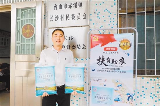 """李荣俊向大家展示赤溪镇长沙村打造的""""海龙湾""""品牌台山大米。"""