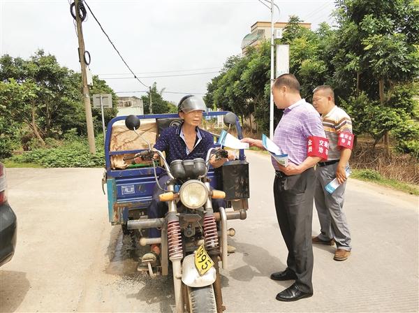 新光村交通安全劝导站劝导员在村道上向驾驶员发放交通安全宣传单。